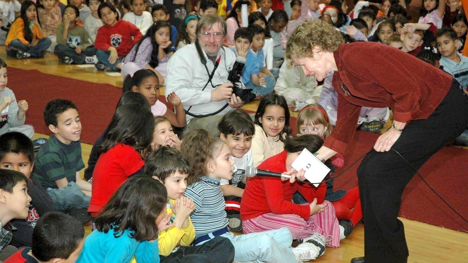 Judy Blume interacts with schoolchildren in an auditorium
