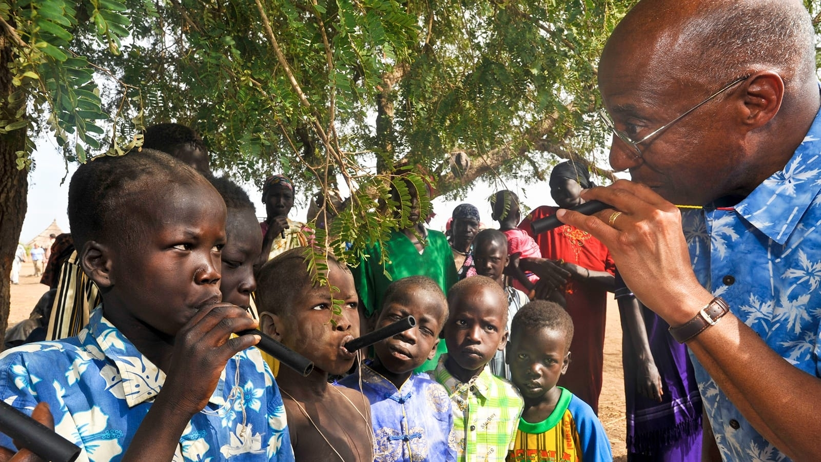 Dr. Donald R. Hopkins shows children in Terekeka County, South Sudan, how to use a portable pipe filter to prevent Guinea worm disease